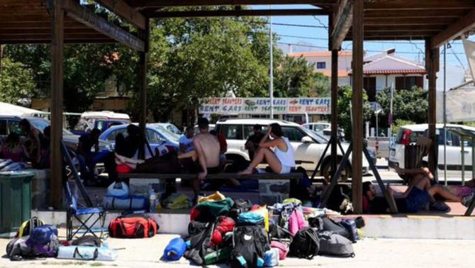 Turisii asteaptă un feribot ca sa plece de pe insula