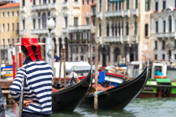 Gondolierii din Veneţia au schimbat tradiţionalele lor pălării cu panglici roşii pentru costume de scafandri