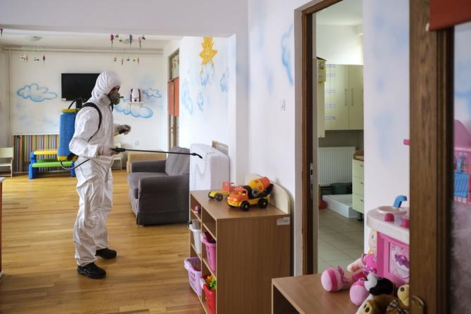 Un lucrător dezinfectează o grădiniță