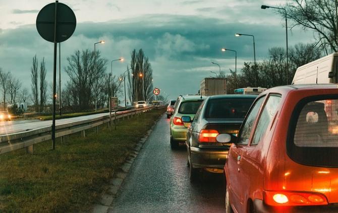 Mai multe maşini aşteaptă cu răbdare la coadă pentru a ajunge lângă automobilul preotului
