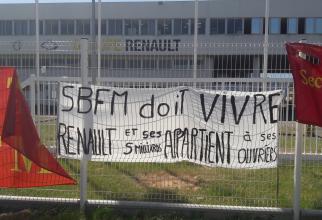 Afișe puse pe gardul uzinei din Maubeuge, Franța, în timpul protestului față de concedierile anunțate