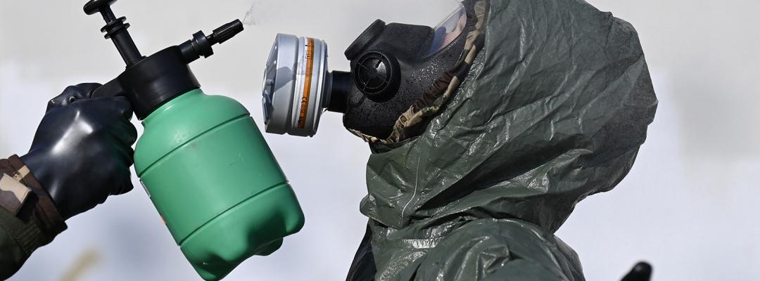 Militari echipați în costume hazmat se dezinfectează