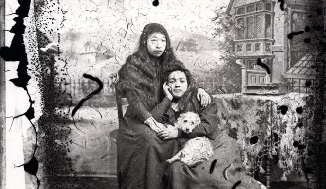 Două tinere amerindiene țin în brate un câine din rasa salish wolly